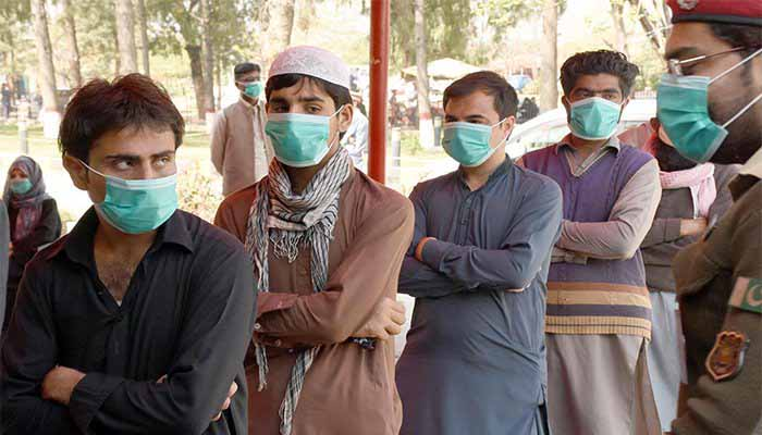 People, wearing face masks, stand in a queue. Photo: File