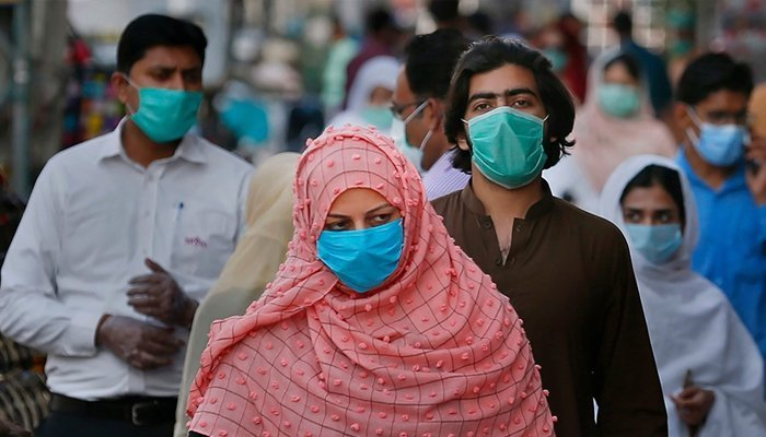Masked people walk in a market amid the fourth wave of the coronavirus pandemic in Pakistan. Photo: AFP