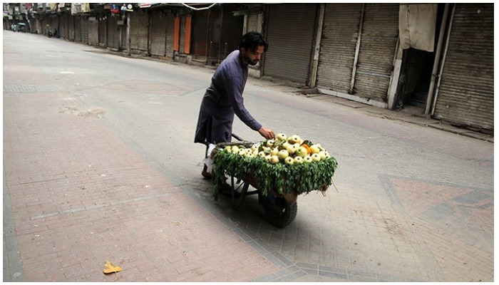 A fruit vendor waits for customers as he sells guava from a wheelbarrow along a closed market during a lockdown, following an outbreak of coronavirus disease (COVID-19), in Lahore, Pakistan. — AFP