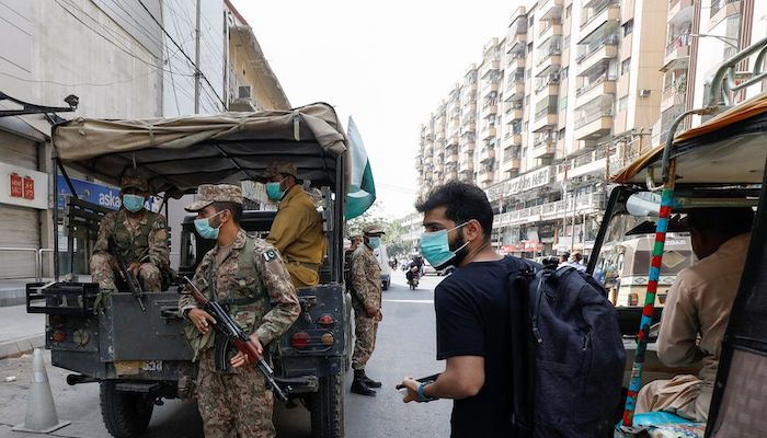 A resident wearing a protective mask walks past Pakistan Army soldiers on patrol to enforce coronavirus disease (COVID-19) safety protocols in Karachi, Pakistan April 28, 2021. Photo: Reuters