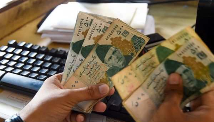 A currency exchange trader counts money at his office in Islamabad. — AFP/File