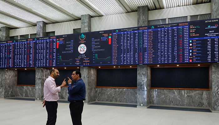 Men are seen talking in front of electronic board displaying share market prices during a trading session at the Pakistan Stock Exchange (PSX) in Karachi. — Reuters