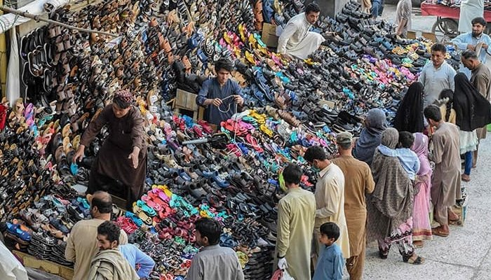 Sellers line up for shoes at a market in Pakistan. Photo: AFP