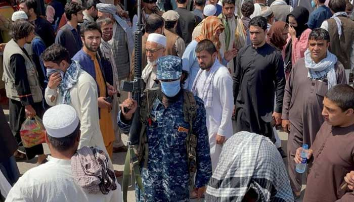 Member of Taliban security forces stands guard among crowds of people in a street in Kabul. — Reuters