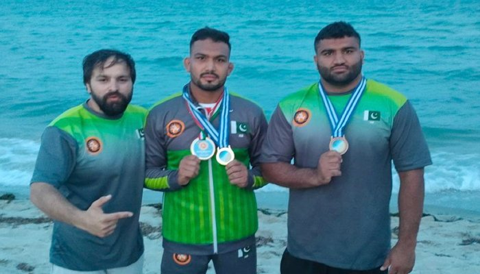 Pakistan's most celebrated wrestler Inam Butt (centre) shows his medal after winning thethird tournament of Beach Wrestling World Series 2021 in Greece, on September 11, 2021. — Geo News