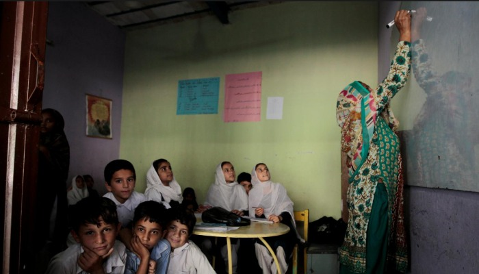 Students look out the door as their teacher writes on the board. September 26, 2017. Courtesy: Reuters.