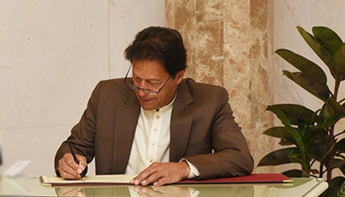 Prime Minister Imran Khan signing a document. Photo: File/ Geo Urdu