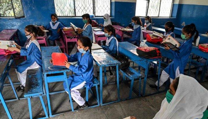 Schoolchildren sit in a class, studying their textbooks. Photo: The News International