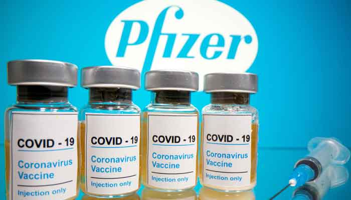 Vials with a sticker reading, COVID-19 / Coronavirus vaccine / Injection only and a medical syringe are seen in front of a displayed Pfizer logo in this illustration taken October 31, 2020. Photo: Reuters