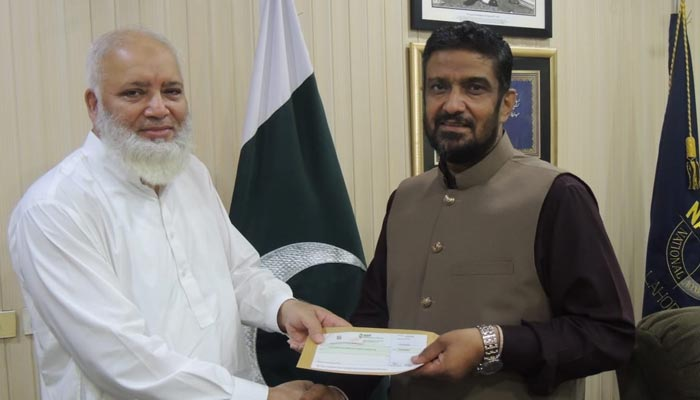 Director-General NAB Lahore Shahzad Saleem (right) handing over Rs11.64 million cheque to NBP official. — NAB handout