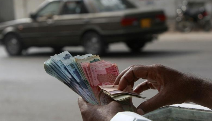 Representational image of a man holding the Pakistani currency notes — Reuters/File