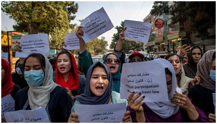 Afghan women converse with a man while they hold placards during a demonstration demanding better rights for women in front of the former Ministry of Women Affairs in Kabul on September 19. — AFP