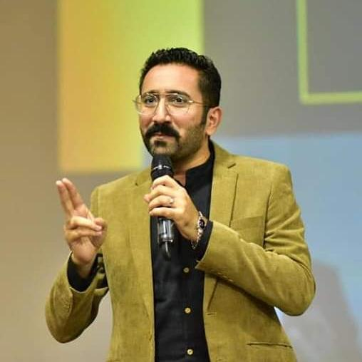 Tanzeel Rauf gestures while speaking.