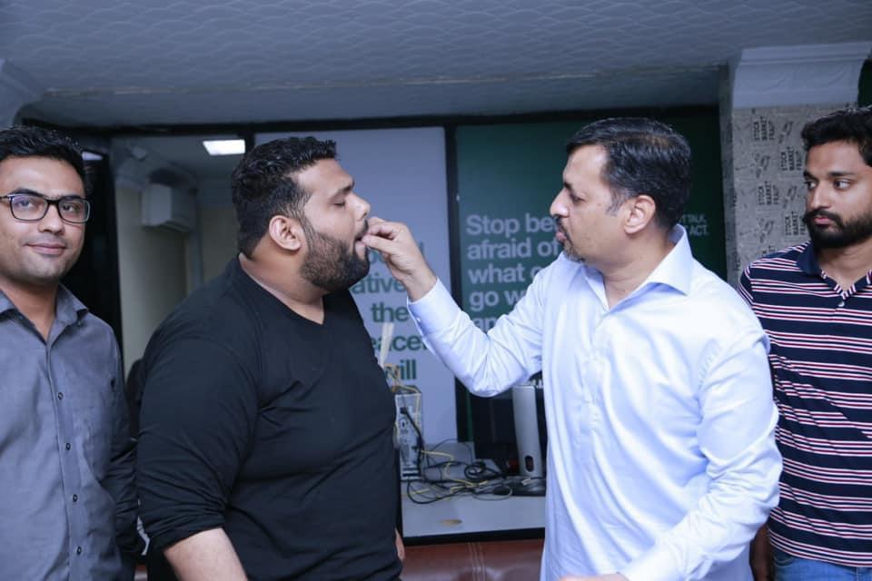 Mustafa Kamal feeds sweets to Nadir Qureshi.