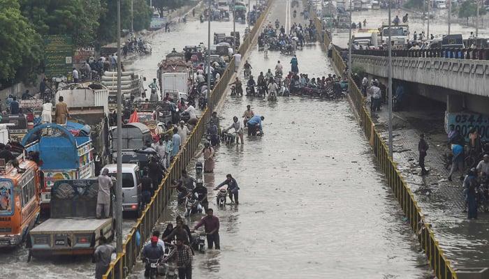 Commuters cross a flooded street after a heavy rainfall in Karachi on September 23, 2021. — AFP