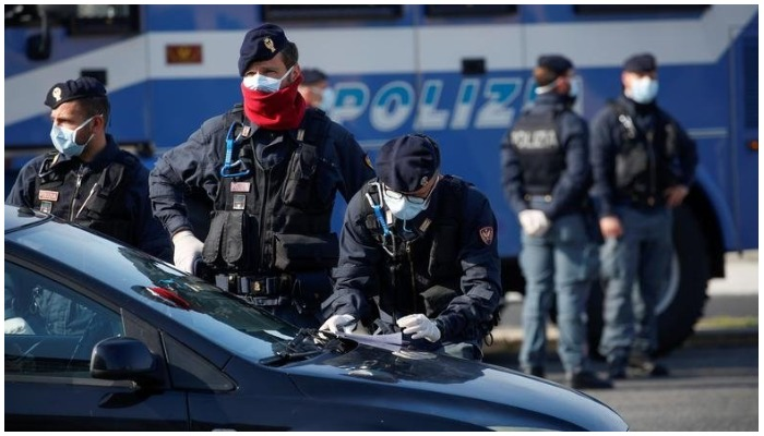 Police officers wearing protective face masks check documents of drivers COVID-19 outbreak in Ostia, near Rome, Italy, April 13, 2020. — Reuters File