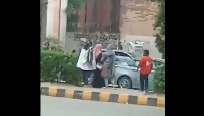 Three women stand near a bus stop as a man tries to interact with them. Photo: Twitter screengrab