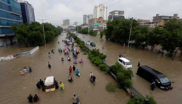 People wade through a flooded road amidst submerged vehicles during monsoon rain in Karachi, August 27, 2020. — Reuters