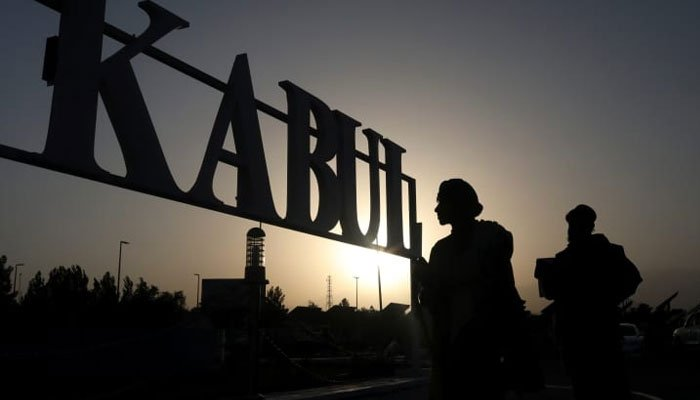 Taliban soldiers stand in front of a sign at the international airport in Kabul, Afghanistan, September 9, 2021. WANA (West Asia News Agency) via REUTERS