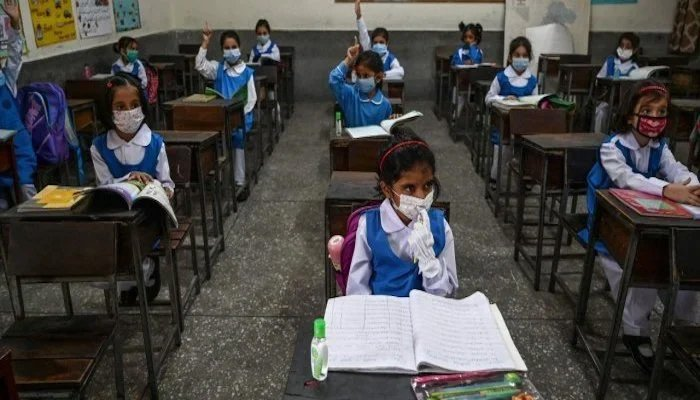 Students of a school in Karachi listen to a lecture wearing face masks. — AFP/File