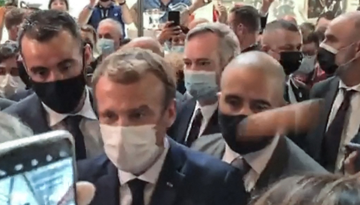 This video grab made from a footage by LyonMag.com shows an egg bouncing on French President Emmanuel Macron´s shoulder— AFP