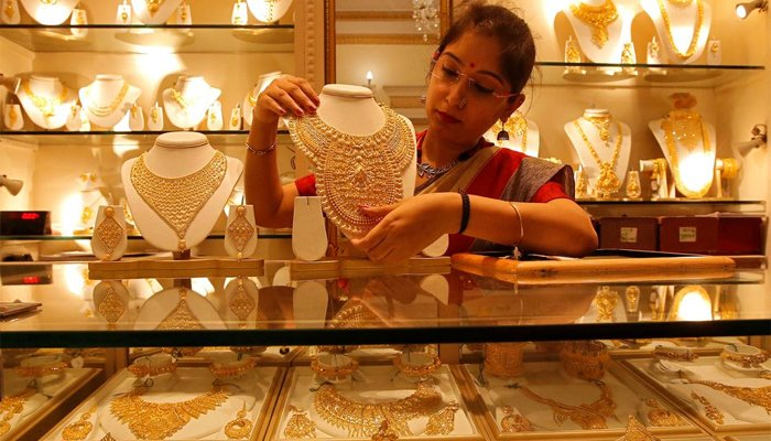 A saleswoman displays a gold necklace inside a jewellery showroom. — Reuters