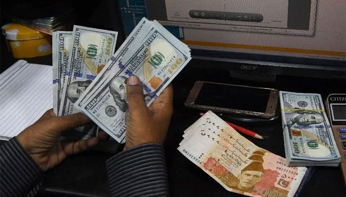 A currency dealer is counting dollar notes while Rs5,000 notes are placed on the desk. — AFP/File