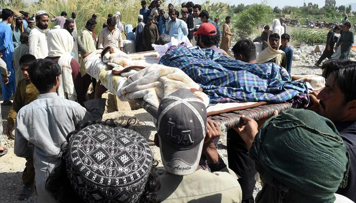 Residents carry the body of a quake victim as they prepare for a burial following an earthquake in the remote mountainous district of Harnai on October 7, 2021. — AFP