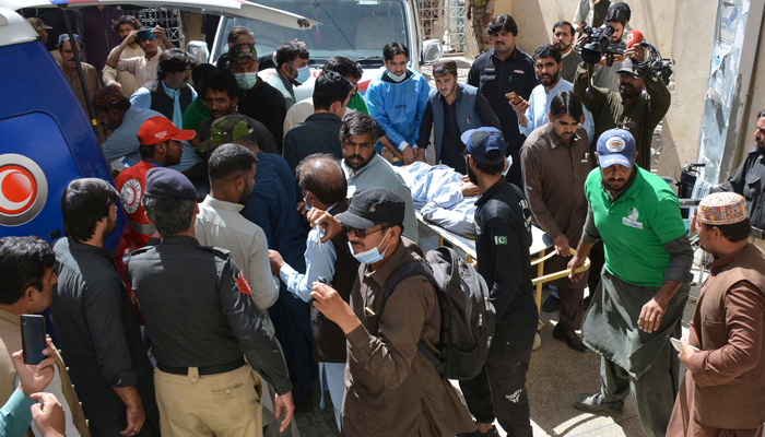 Volunteers move starchers carrying injured victims to a hospital in Quetta on October 7, 2021. — AFP