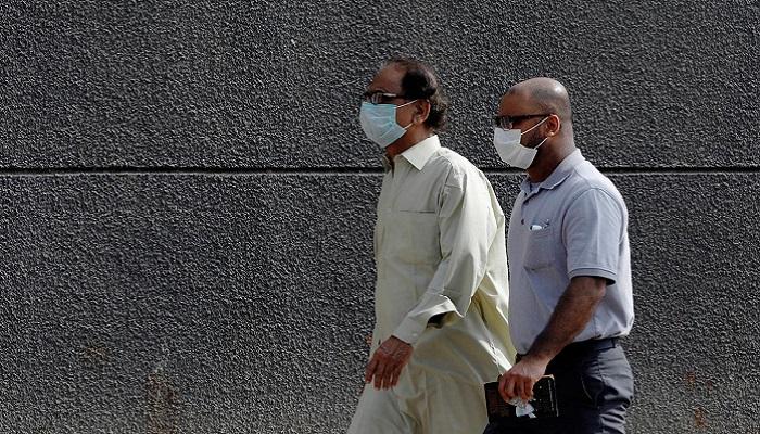 Men walk with face masks as a preventive measure against coronavirus along a sidewalk in Karachi, Pakistan. Photo: Reuters