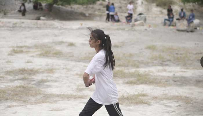 A girl prepares to bowl during the cricket tournament.