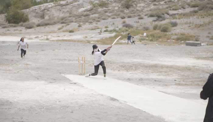 A girl plays an aggressive shot during a cricket tournament.