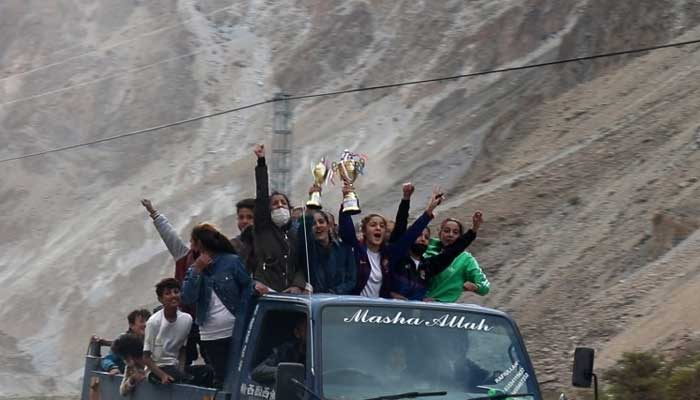 The victors of the tournament celebrate atop a vehicle with their trophies.