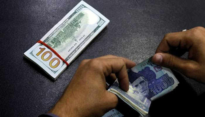 A currency dealer is seen counting Rs1,000 notes while a stack of dollar is placed on the table. — AFP/File