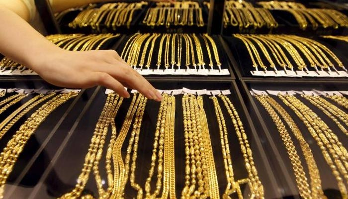 An employee arranges gold jewellery in the counter at a gold shop in Wuhan, Hubei province, in August 25, 2011. — REUTERS/File