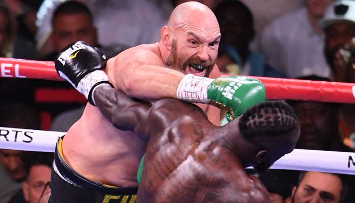 WBC heavyweight champion Tyson Fury of Great Britain (L) lands a punch on US challenger Deontay Wilder (R) in the third round fight for the WBC/Lineal Heavyweight title at the T-Mobile Arena in Las Vegas, Nevada, October 9, 2021. — Photo by Robyn Beck/AFP