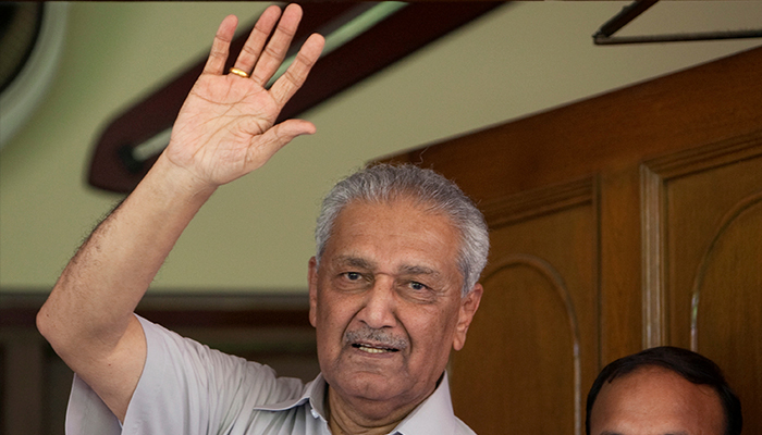 Pakistan nuclear scientist Abdul Qadeer Khan waves to journalists from the front door of his house in Islamabad on August 28, 2009. — Reuters