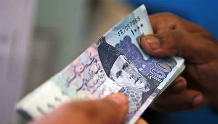 Currency dealer can be seen exchanging Rs1,000 note. — AFP/File